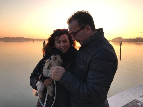 Coppia di innamorati con yorkshire terrier in braccio al tramonto